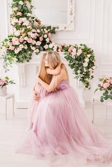 Retrato de uma mãe e filha em vestidos elegantes em um belo interior com flores.