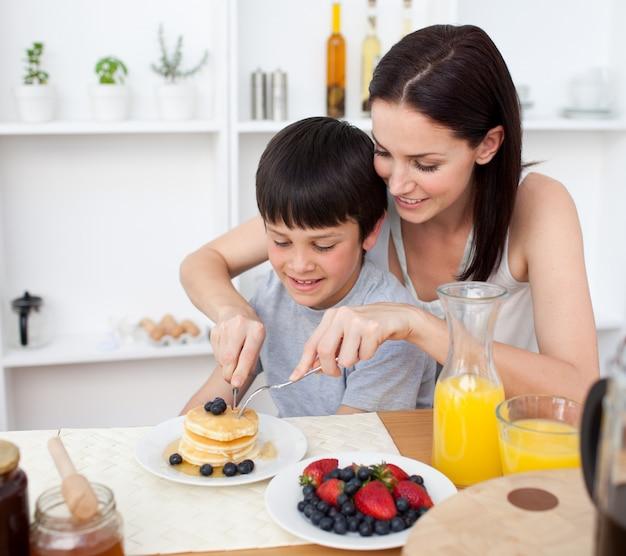 Retrato de uma mãe e seu filho comendo panquecas no café da manhã