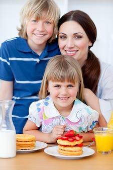Retrato de uma mãe e seus filhos tomando café da manhã