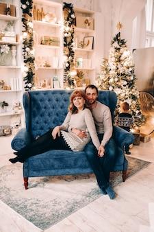 Retrato de uma mãe e um pai amorosos segurando seu filho fofo e adorável, vestindo um suéter estampado de inverno
