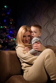 Retrato de uma mãe feliz e adorável bebê brincando em casa no fundo de uma árvore de natal.