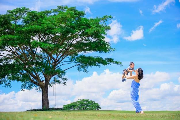 Retrato de uma mãe feliz e amorosa com seu bebê ao ar livre