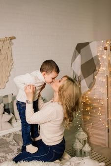 Retrato de uma mãe feliz e um bebê adorável celebram o natal. feriados de ano novo.