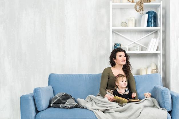 Retrato de uma mãe sorridente e fofa e linda lendo um livro em um quarto branco brilhante e branco