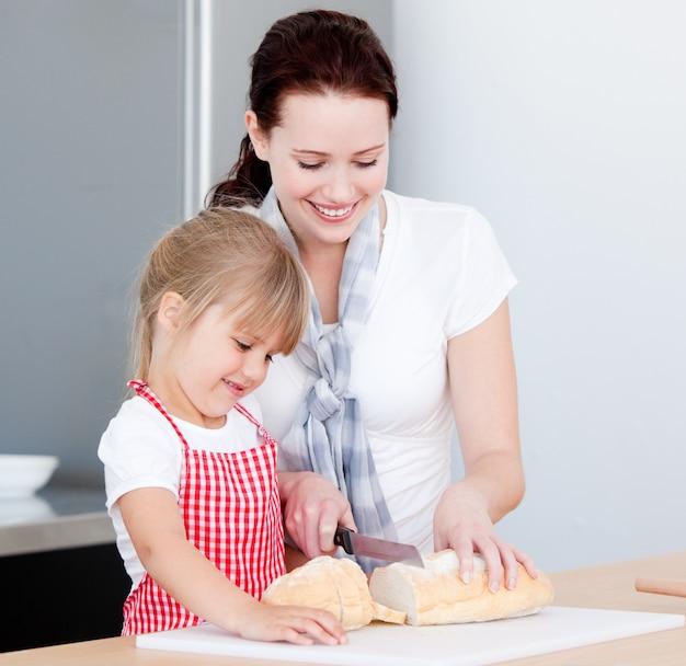 Retrato de uma mãe sorridente e sua filha preparando uma refeição