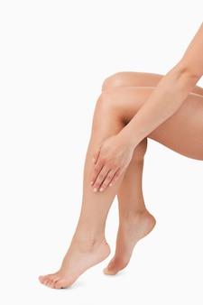 Retrato de uma mão feminina tocando pernas