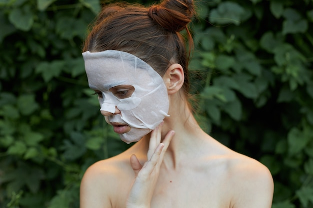 Retrato de uma máscara facial de menina olha para baixo e segura a mão dele perto do pescoço, ombros nus, arbustos verdes ao fundo