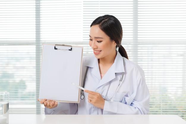 Retrato de uma médica asiática apontando para a área de transferência enquanto está sentado no consultório