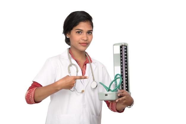 Retrato de uma médica com instrumento de pressão arterial e estetoscópio sobre fundo branco.