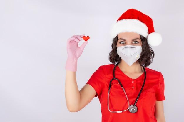 Retrato de uma médica com uma máscara de proteção médica chapéu de papai noel e luvas de nitrilo rosa mão com a imagem de um coração, um símbolo da cardiologia do amor