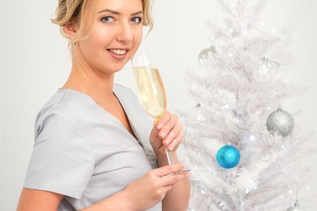 Retrato de uma médica com uma taça de champanhe em pé perto da árvore de natal
