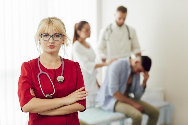 Retrato de uma médica loira com um uniforme vermelho com um estetoscópio.