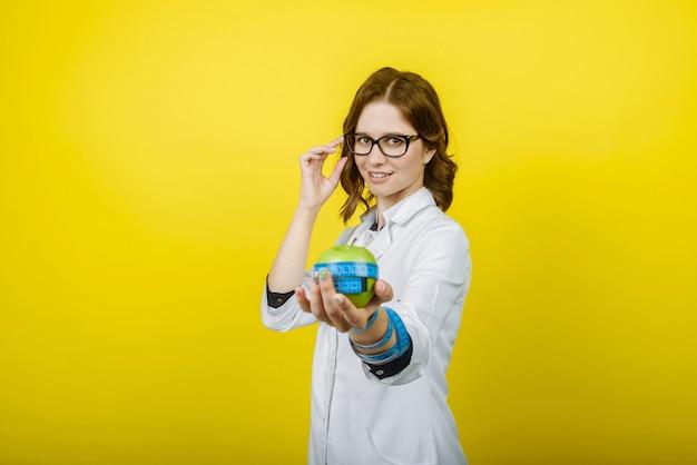 Retrato de uma médica nutricionista sorridente em um vestido branco com um estetoscópio segurando uma fita métrica e uma maçã isolada