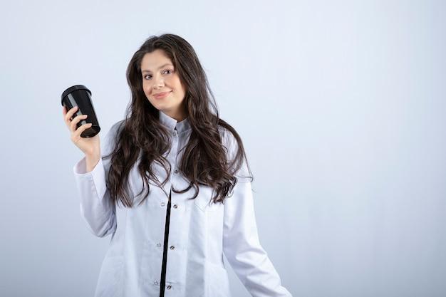 Retrato de uma médica posando com uma xícara de café na parede branca.