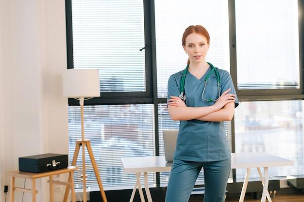 Retrato de uma médica séria em uniforme verde azul em pé no fundo da janela em um dia ensolarado no escritório da clínica médica.