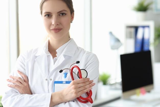 Retrato de uma médica sorridente de jaleco branco em um consultório médico