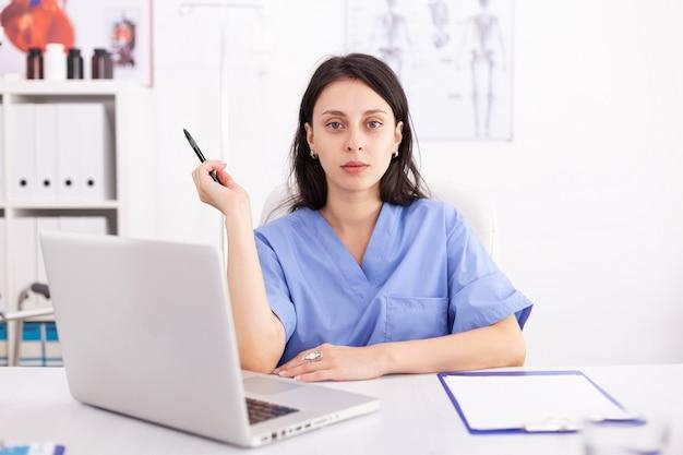 Retrato de uma médica usando seu laptop na clínica. médico usando notebook no local de trabalho do hospital, confiante, experiência, medicina.
