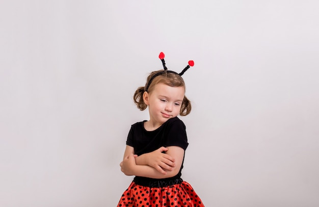 Retrato de uma menina, abraçando-se em uma fantasia de joaninha