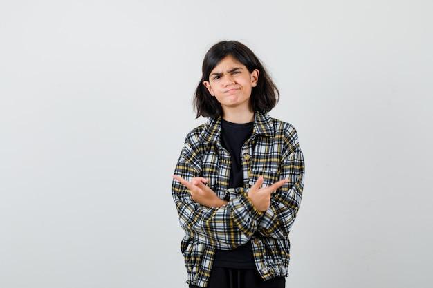 Retrato de uma menina adolescente apontando para direções opostas com as mãos cruzadas em uma camisa casual e olhando a vista frontal indecisa