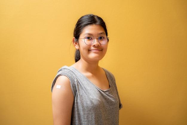 Retrato de uma menina adolescente asiática feliz após receber a injeção da vacina covid-19 e mostrando o curativo no braço, menina tailandesa, vacinada