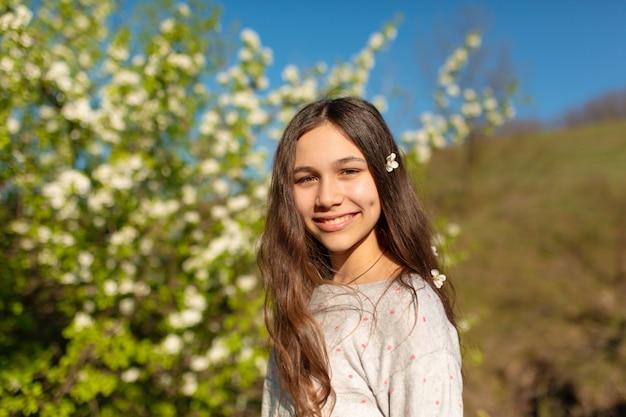Retrato de uma menina adolescente bonita em um jardim de primavera verde florescendo
