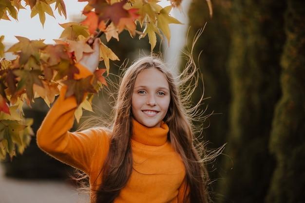 Retrato de uma menina adolescente bonita que levanta em um fundo do outono. copie o espaço.