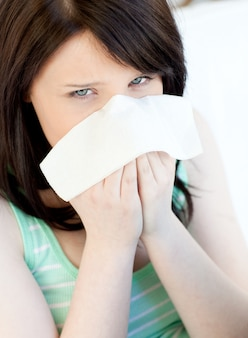 Retrato de uma menina adolescente caucasiano doente soprando