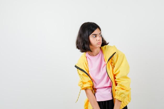 Retrato de uma menina adolescente olhando para o lado em uma camiseta, jaqueta e parecendo chocada com a vista frontal