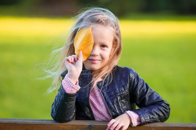 Retrato de uma menina adorável com folhas amarelas ao ar livre no lindo dia de outono