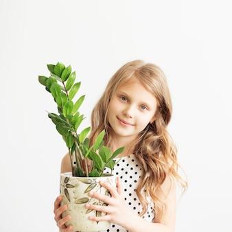 Retrato de uma menina adorável com planta de casa verde sobre um fundo branco