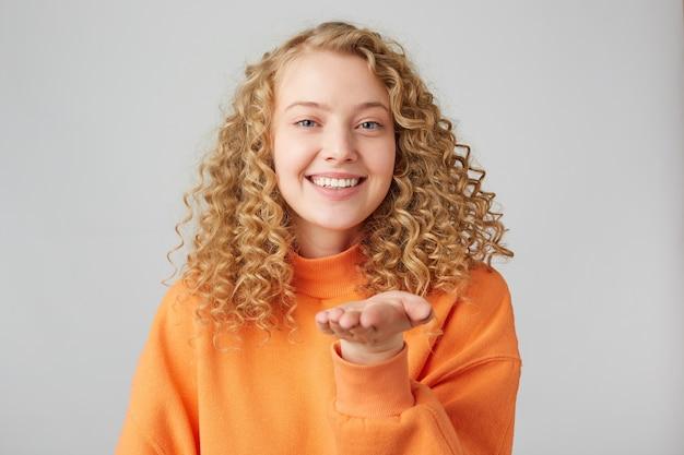 Retrato de uma menina adorável e doce com penteado moderno sorrindo soprando beijo no ar com beicinho lábios duas palmas na frente isolado na parede amarela demonstra sentimentos para o namorado