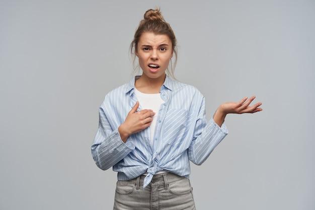 Retrato de uma menina adulta, descontente, com cabelos loiros presos em um coque. vestindo camisa listrada com nó. apontando para si mesma, franze a testa e encolhe os ombros. olhando para a câmera, isolada sobre uma parede cinza