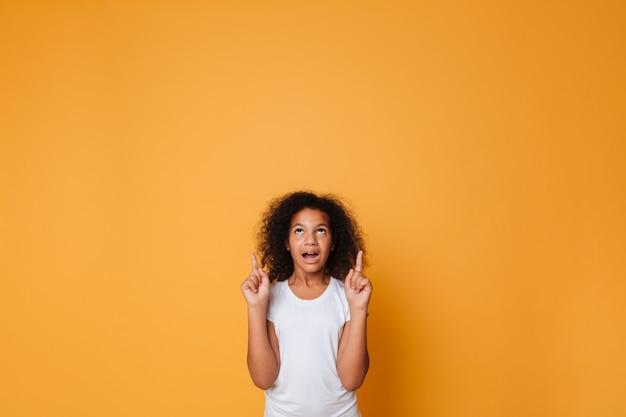 Retrato de uma menina africana animada apontando o dedo para cima