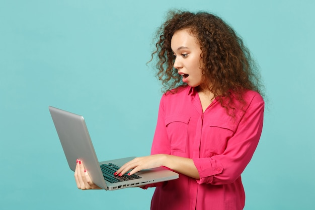 Retrato de uma menina africana chocada em roupas casuais rosa, usando o computador laptop pc isolado no fundo da parede azul turquesa no estúdio. emoções sinceras de pessoas, conceito de estilo de vida. simule o espaço da cópia.