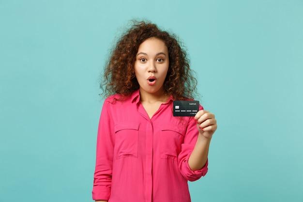 Retrato de uma menina africana chocada em roupas rosa casuais, segurando o cartão do banco de crédito isolado no fundo da parede azul turquesa no estúdio. emoções sinceras de pessoas, conceito de estilo de vida. simule o espaço da cópia.