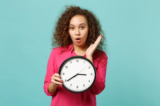 Retrato de uma menina africana espantada e chocada em roupas rosa casuais, segurando o relógio redondo isolado no fundo da parede azul turquesa no estúdio. emoções sinceras de pessoas, conceito de estilo de vida. simule o espaço da cópia.