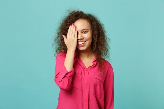Retrato de uma menina africana sorridente em roupas casuais rosa, cobrindo o rosto com a mão isolada no fundo da parede azul turquesa no estúdio. emoções sinceras de pessoas, conceito de estilo de vida. simule o espaço da cópia.