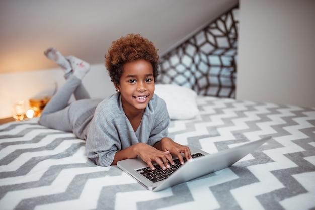 Retrato de uma menina afro-americano de sorriso bonita que usa o portátil na cama.