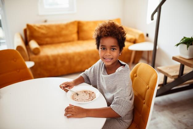 Retrato de uma menina afro-americano de sorriso bonito que come o café da manhã.