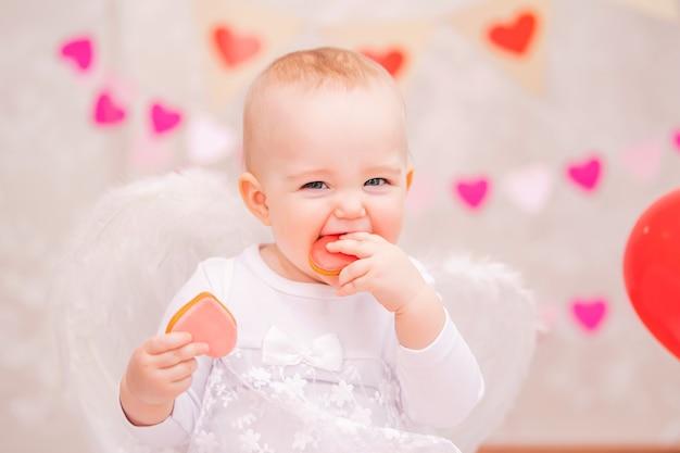Retrato de uma menina alegre com asas de penas brancas comendo biscoitos em forma de coração