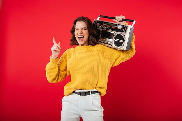 Retrato de uma menina alegre com um boombox