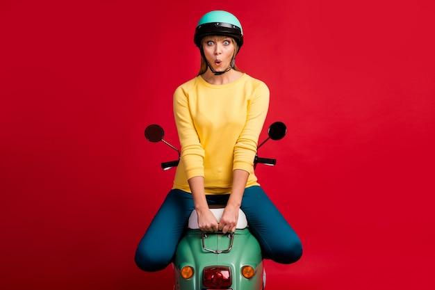 Retrato de uma menina alegre e espantada sentada no rosto chocado de ciclomotor na parede vermelha