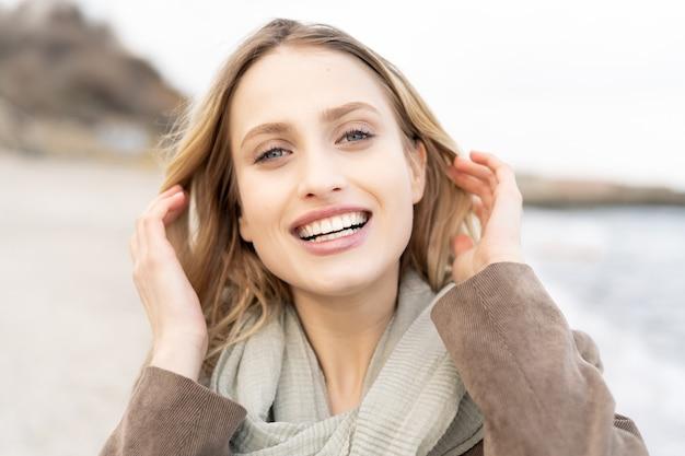 Retrato de uma menina alegre e feliz sorrindo e arrumando o cabelo loiro durante o pôr do sol