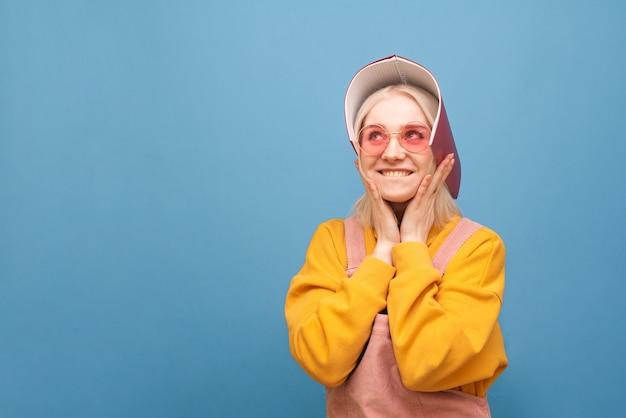 Retrato de uma menina alegre em óculos cor de rosa e um caderno na cabeça, olhando para longe e sorrindo