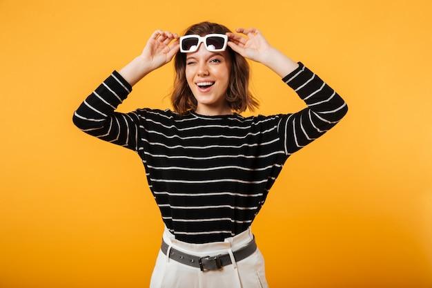 Retrato de uma menina alegre em óculos de sol piscando