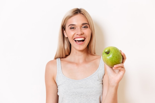 Retrato de uma menina alegre em roupa interior, mostrando a maçã verde