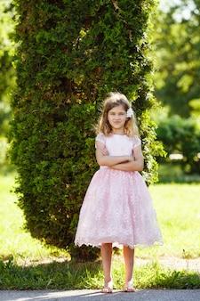 Retrato de uma menina alegre em um vestido rosa exuberante no parque.