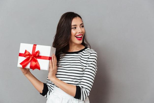 Retrato de uma menina alegre, segurando a caixa de presente