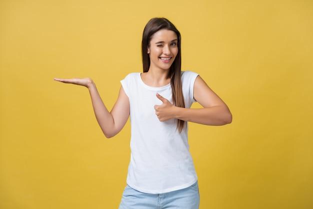 Retrato de uma menina alegre segurando copyspace na palma da mão isolada em um fundo amarelo