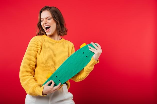 Retrato de uma menina alegre, segurando o skate